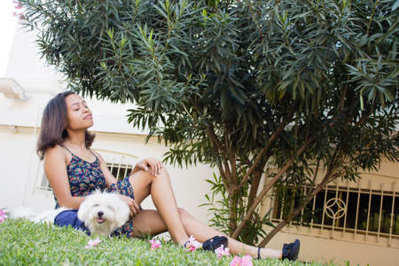 Woman sitting on the grass with her dog