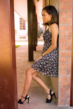 Woman leaning against the wall with flexed legs Stockfoto