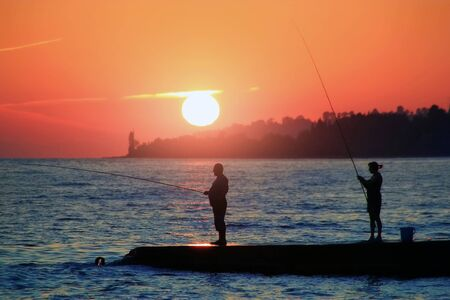 A man with his wife fishing with fishing rods at sea, stand on the pier during sunset.