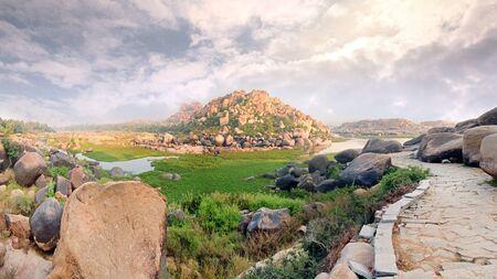 India Hampi, a hill near the river and a stone path