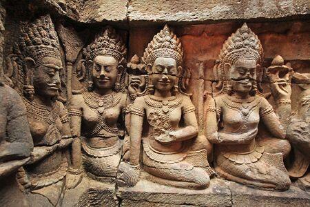 Three women sculptures at a temple at Angkor Wat, detail of carvings, Cambodia.