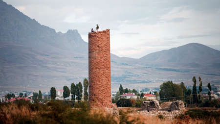 Two young men stand on top of the ruined of the medieval Osman Mosque and its minaret in the Old City of Van against the backdrop of mountains, near the famous Van Fortress, Van, Turkey.