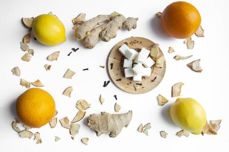 Fruit. Ginger orange lemon and lumps of sugar on a wooden saucer, all on a white background.