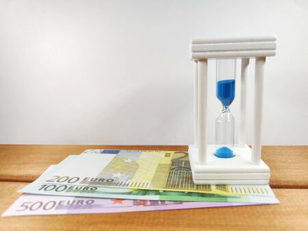 Euro coins, bundles of cash bills and an hourglass with blue sand, on a wooden background, the concept of business development from time to time. With copy space.