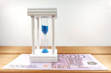 Euro coins, bundles of cash bills and an hourglass with blue sand, on a wooden background, the concept of business development from time to time. With copy space. Stock Photo