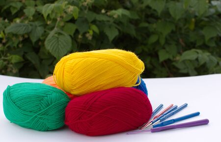 balls of multicolored woolen threads for knitting, lying on the table, against the background of green leaves.
