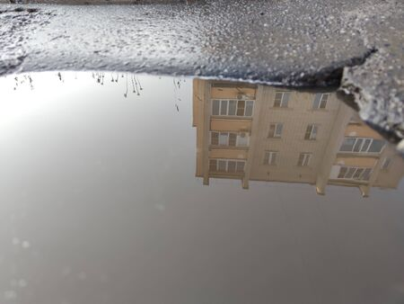 Reflecting the house in a normal street puddle of water. Standard-Bild - 150478366