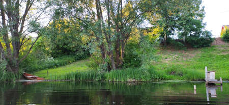 The pesage, the green bank of the river with trees and a strapped boat, the reflection of the shore in the water.