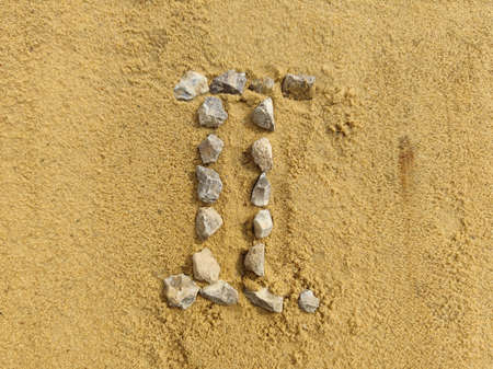 the Roman numeral 2 is laid out with stones on the river sand.