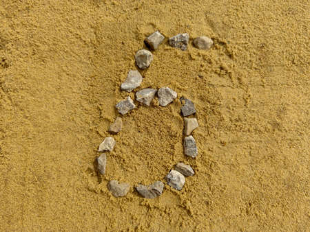 Number 6 on the sand, laid with fine gravel 免版税图像