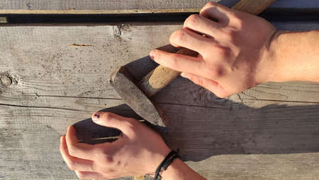 A hammer and a finger with a black bruised nail against the background of an old wooden table. very painfully. 免版税图像 - 151000472