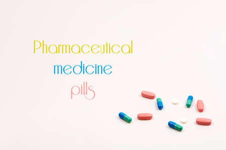 multicolored tablets and capsules lie in a white background. inscription Pharmaceutical medicine pills Stock fotó