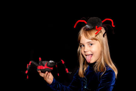 Little devil with a huge spider on his head and in his hands on a black background. The girl shows her tongue. Halloween costume.