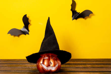 Halloween orange pumpkin with witch hat on dark background with bats.