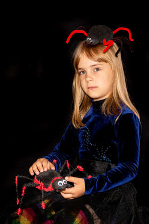 Little devil with a huge spider on his head and in his hands on a black background. The girl is angry. Halloween costume.