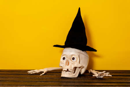 Happy Halloween. Skull and crossbones in a hat on a yellow background. the concept of Halloween