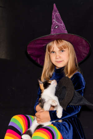 Little witch in a huge hat on her head on a black background. The girl is holding a three-haired cat. Halloween costume. 免版税图像