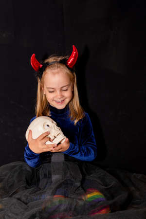 Little witch in a huge hat on her head on a black background. The girl is holding a silver skull. Halloween costume.