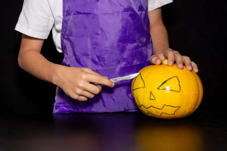 child carves a scary face in a pumpkin. Happy Halloween.