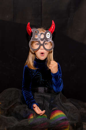 A little devil with red horns and glasses that say Boo on a black background. costume for Halloween.