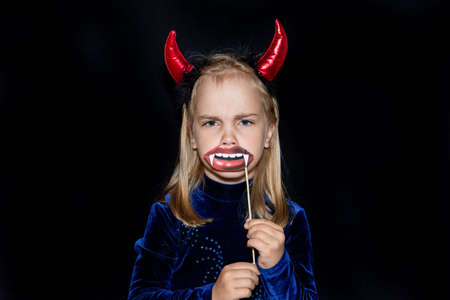 A little devil with red horns and vampire fangs on a black background. costume for Halloween.