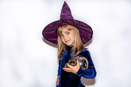Little witch in a huge hat on her head on a white background. The girl is holding a silver skull. Halloween costume.