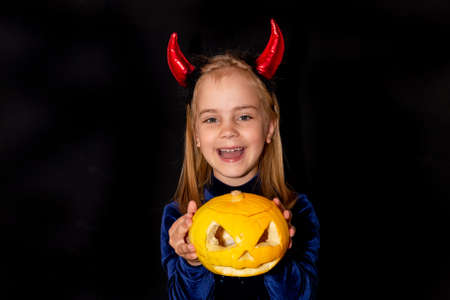 A little devil with red horns and a pumpkin with a scary face on a black background. costume for Halloween. 免版税图像