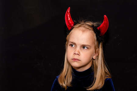 A little devil with red horns on a black background. costume for Halloween.
