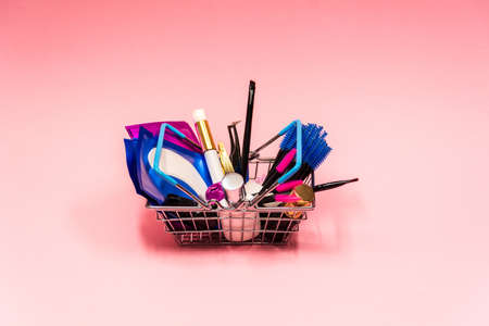 eyelash extension kit in a small grocery basket on pink background. The concept of beauty. 免版税图像