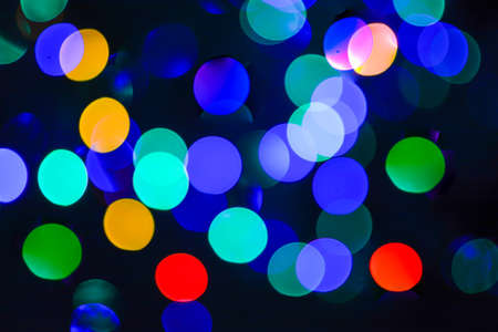 Multi-colored abstract bokeh background on a black background. Creative design.
