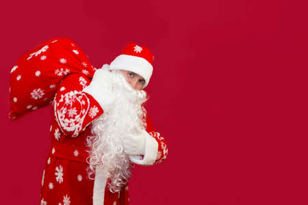 Santa holds a bag of gifts behind his back on a red