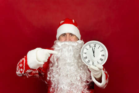 Santa is holding a white clock that says its two minutes to twelve.