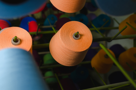 Textile industry - yarn spools on spinning machine in a textile factory Stock Photo