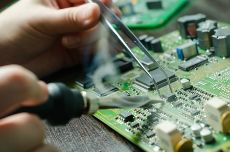 Male hands close up soldering a microchip. tools