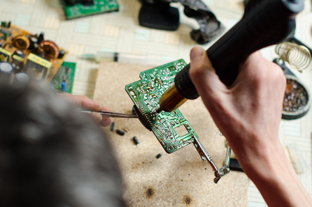 Closeup of a technicians hands soldering a electronic devices. top view