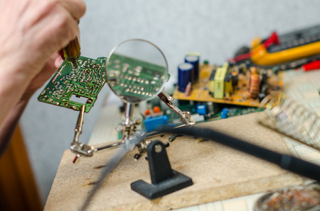 Engineer soldering microcircuit though magnifier. third hand, tools