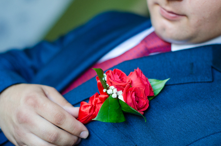 man in a dark blue suit corrects hand of a red rose boutonniere