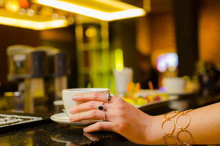 Womans hands hugging a cup of coffee in a restaurant.