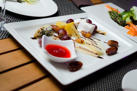 チーズ プレートを添えてブドウ、ジャム、白いプレートのナット。