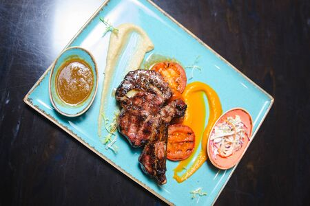 Grilled steaks and vegetables and sauce on blue plate. Zdjęcie Seryjne