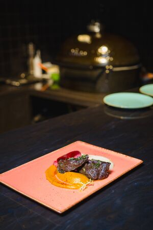 Grilled beef with sause on a pink plate
