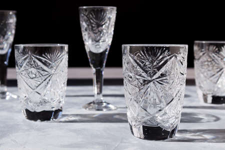 Crystal glasses on textured table with hard light and long clear shadow. Sun glare, light refraction on transparent faceted dishes. Horizontal photo, gray color, black background