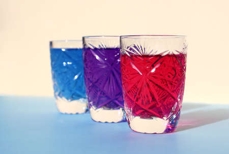 Three crystal glasses with bright neon drinks. Blue, beige background. Food coloring, paint mixing. Purple, pink, turquoise water. Sunlight, glare, highlights on faceted dishes 写真素材
