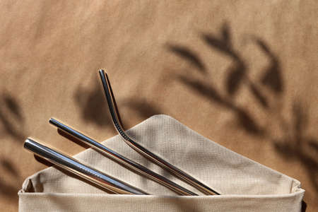 Reusable stainless steel straws in textile bag on kraft background, hard light. Zero waste, no plastic concept. Metal tool for eco friendly lifestyle. Horizontal brown banner with copy space, flat lay