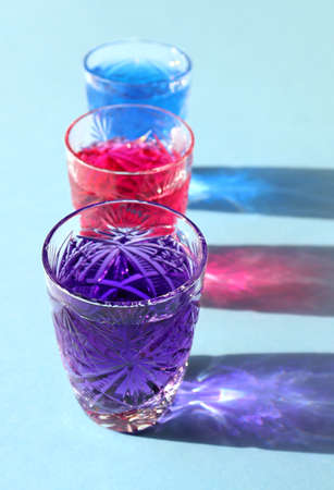 Vertical image of three bright violet, pink, turquoise fairy drink. Colored alcoholic cocktail or syrup. Crystal glasses with neon liquid on blue background. Hard sunlight trend, glare, long shadow