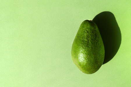 Green Avocado on textured paper background. Nature concept. Horizontal poster, banner with copy space. Whole raw fruit. Healthy organic food. Hard sunlight trend, long shadow, monochrome, flat lay 写真素材