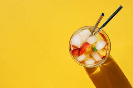 Peach cocktail with metal straws on bright yellow background. Horizontal banner, poster with copy space. Summer cold drink with ice, mint, fruit in glass. Hard sunlight trend, long shadow, flat lay 写真素材