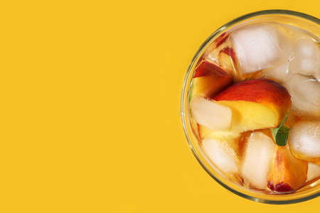 Peach cocktail with ice on bright yellow background. Horizontal banner, poster with copy space for advertising summer holiday, sales. Cold drink with mint, pieces of fruit in glass. Flat lay