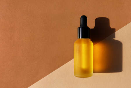 Cosmetic oil bottle, double diagonal background. Horizontal mockup, banner, poster, copy space. Yellow serum, extract, emulsion, eco lotion. Brown terracotta colors. Hard light, dark shadow, flat lay
