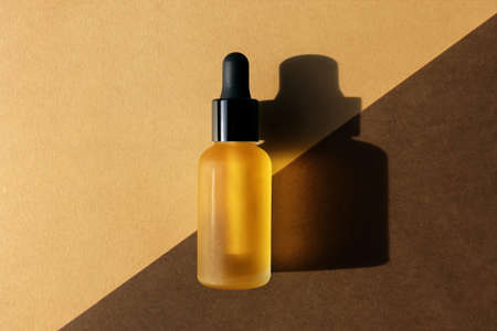 Dropper oil bottle on diagonal background, flat lay. Monochrome brown mockup, banner, poster. Natural cosmetic, eco lotion, essence, serum, emulsion. Body care concept. Hard light, central composition 版權商用圖片